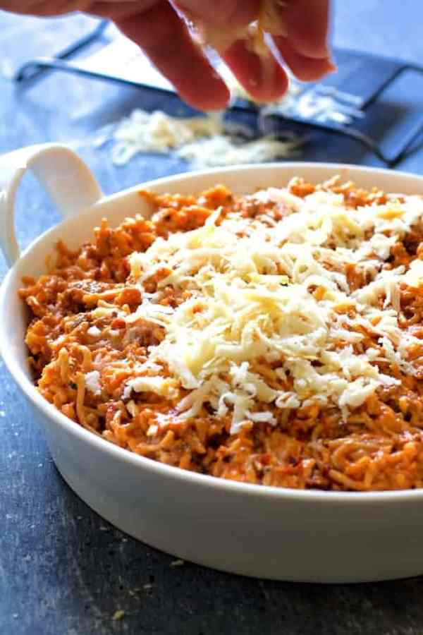 Spaghetti Pie with Three Cheeses - Cheese being sprinkled over dish