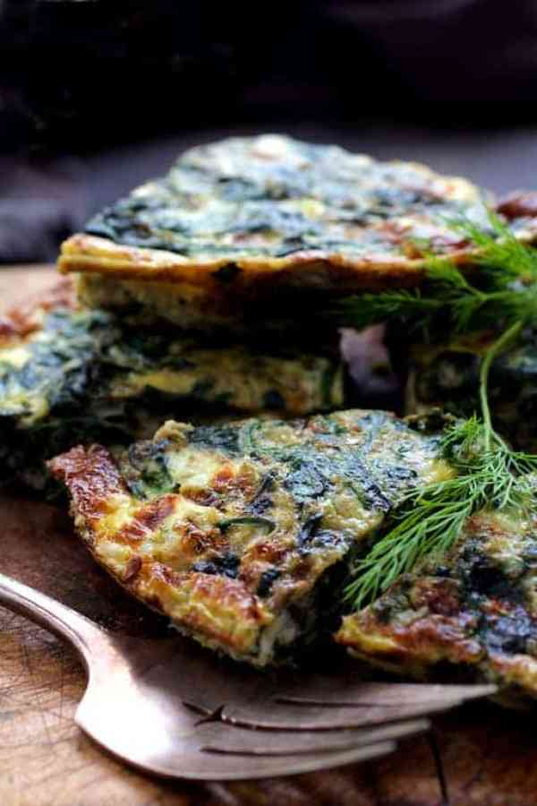 Spinach Leek and Feta Cheese Frittata - Pieces of frittata piled up on wood trivet