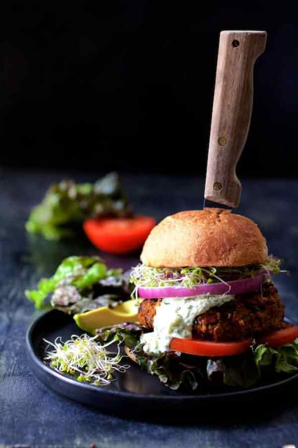 Lentil Walnut Veggie Burgers with Avocado Tzatziki - Hero shot of burger on black plate with knife through burger