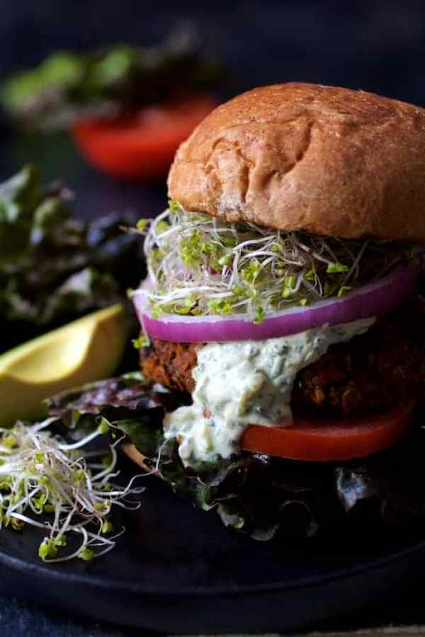 Lentil Walnut Veggie Burgers with Avocado Tzatziki - Close-up shot with tzatziki dripping down side of burger
