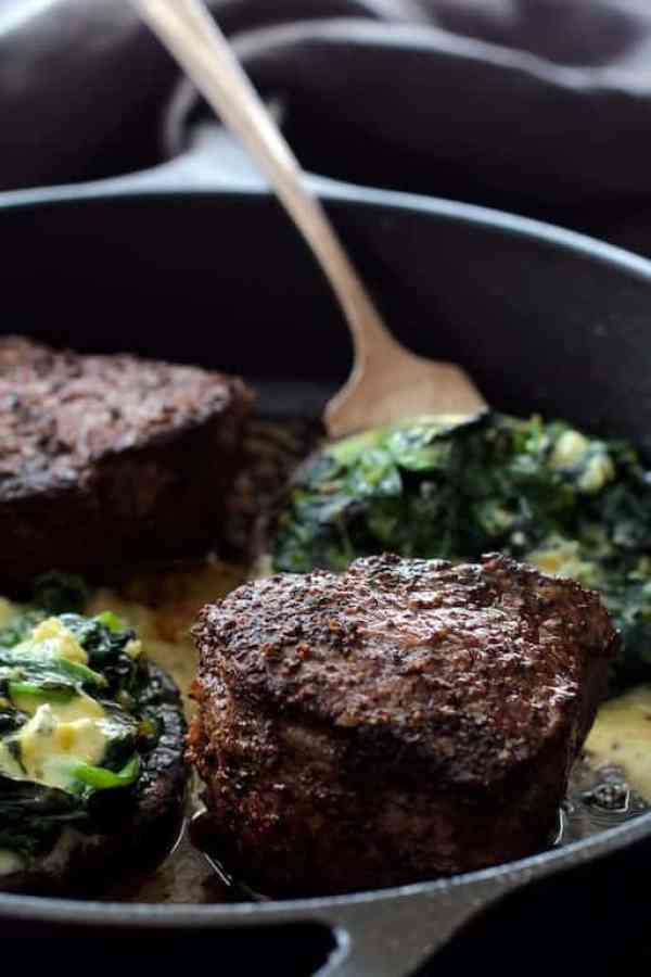 Beef Tenderloin Fillets with Spinach Cambozola Stuffed Mushrooms and Red Wine Sauce - Steaks and mushrooms being cooked together in cast iron skillet