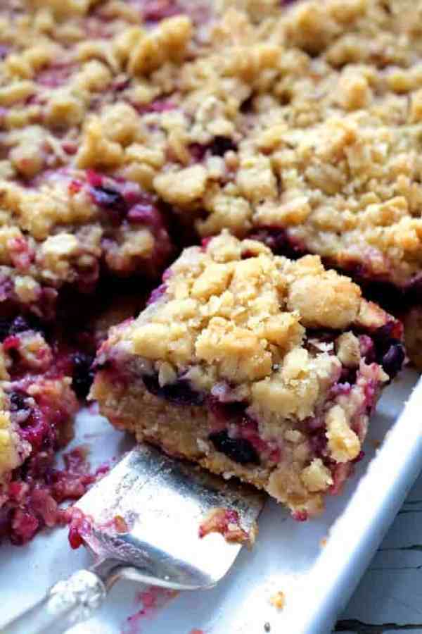 Blueberry Crumble Bars - Close-up shot of bar being removed on silver pie server