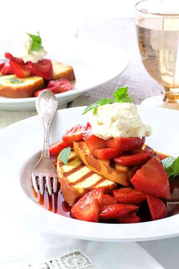 Grilled Pound Cake with Balsamic Macerated Strawberries and Mascarpone Cream - Shot of finished dessert on white plate with water glass in the background