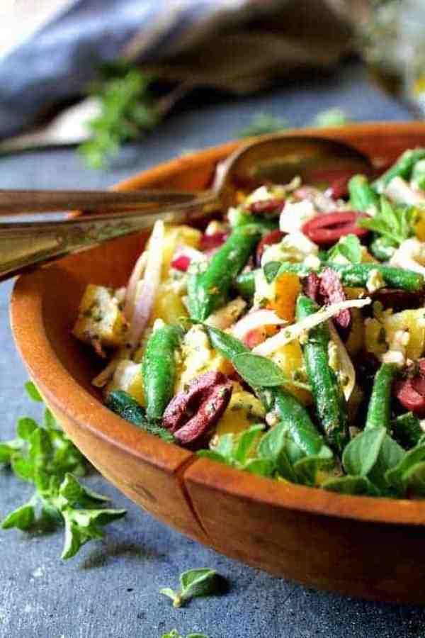 Potato Green Bean Salad with Olives and Feta Cheese - Hero shot of salad in wood salad bowl garnished with fresh oregano