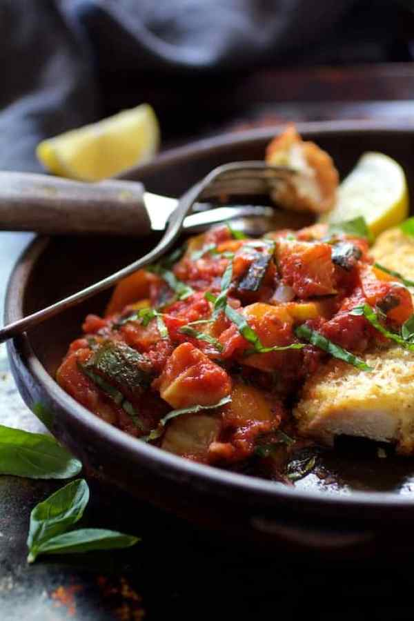 Chicken Scallopini with Roasted Vegetable Ratatouille - Close-up shot of the ratatouille in clay dish with fork and knife