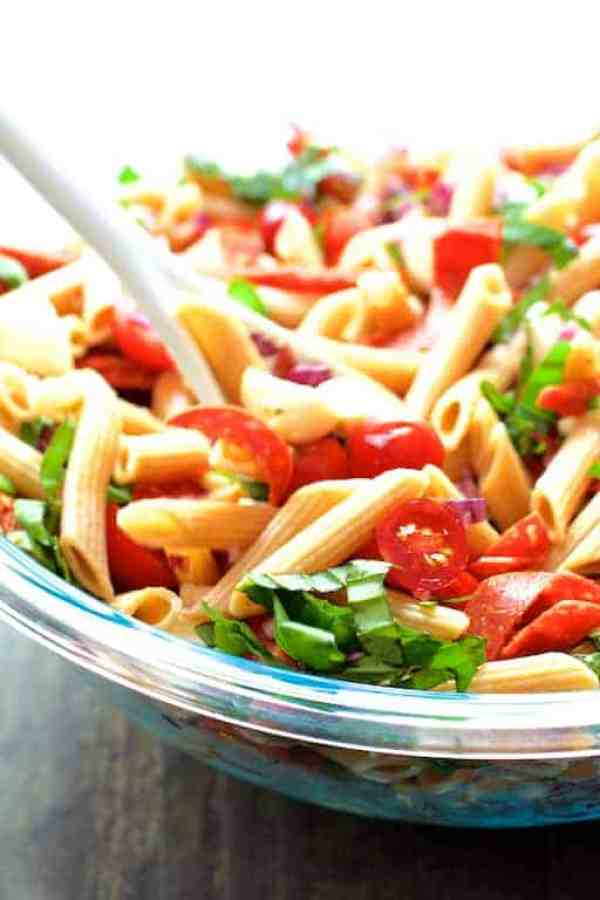 Caprese Pizza Pasta Salad - Salad being stirred with white spoon in glass mixing bowl