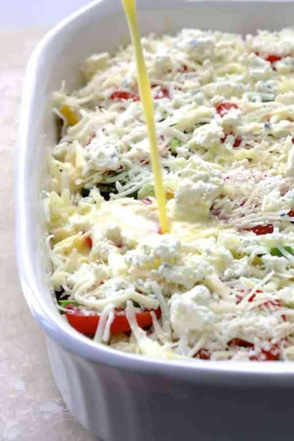 Four Cheese Strata with Zucchini and Tomatoes - Egg mixture being poured into strata before baking