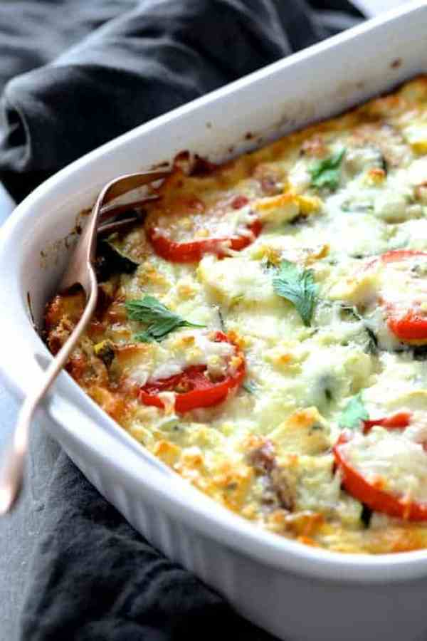 Four Cheese Strata with Zucchini and Tomatoes - Finished strata with pan on an angle on gray towel with serving fork