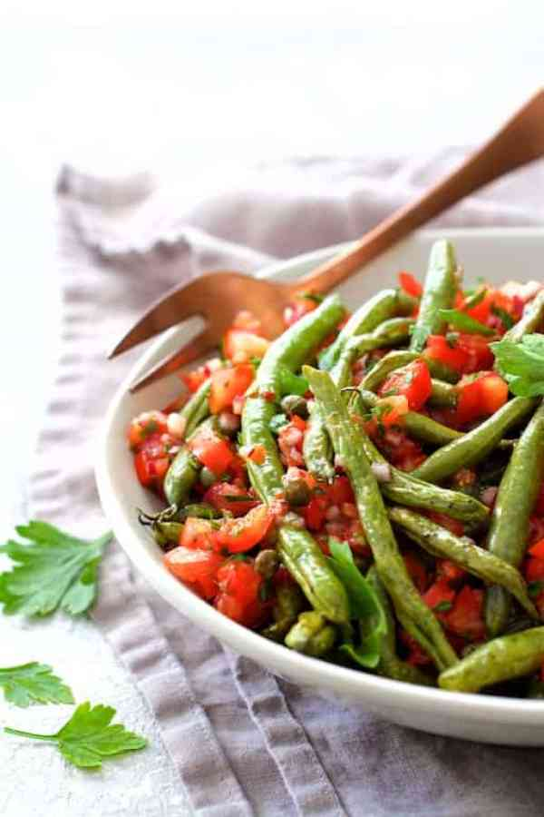 Roasted Green Beans with Tomato Caper Relish - Hero shot of dish in white serving bowl on light gray napkin with copper serving fork garnished with fresh parsley leaves