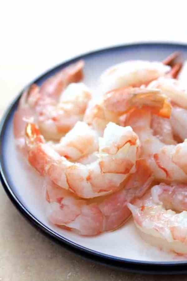Shrimp in Avocado Butter - Fresh, uncooked shrimp on white plate with blue rim