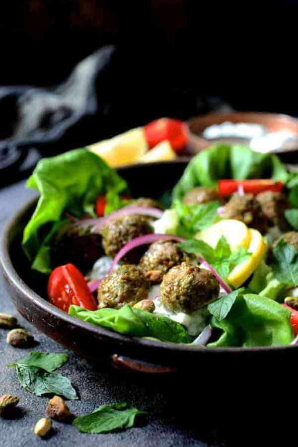 Turkish Turkey Meatball Lettuce Wraps with Tzatziki - Close-up straight-on shot of meatballs in clay dish with all the garnishes: Tomatoes, onion slices, lemon wedges, pistachios, mint leaves