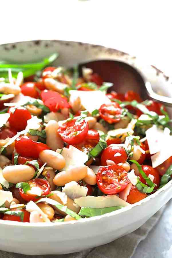 Tuscan Cherry Tomato and White Bean Salad - Close-up shot of salad in white bowl with serving spoon