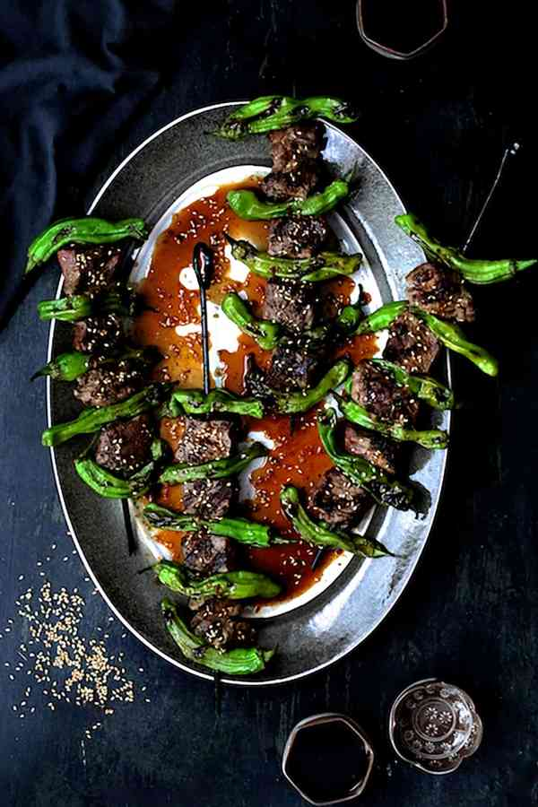 Japanese Beef and Shishito Pepper Skewers - Overhead shot of skewers on gray-rimmed platter garnished with sesame seeds