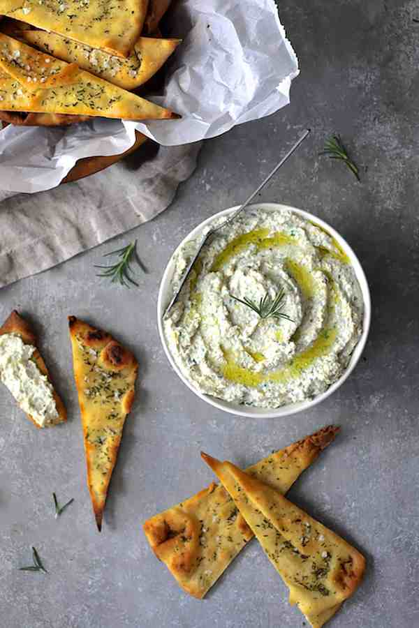 White Bean Artichoke Spread with Rosemary Sea Salt Flatbread Chips - Overhead shot of spread with rosemary chips garnished with rosemary sprigs