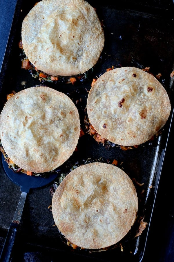 Sheet Pan Quesadillas with Sweet Potatoes, Poblanos and Black Beans with Chipotle Sour Cream - Overhead shot of four assembled and baked quesadilla on baking sheet
