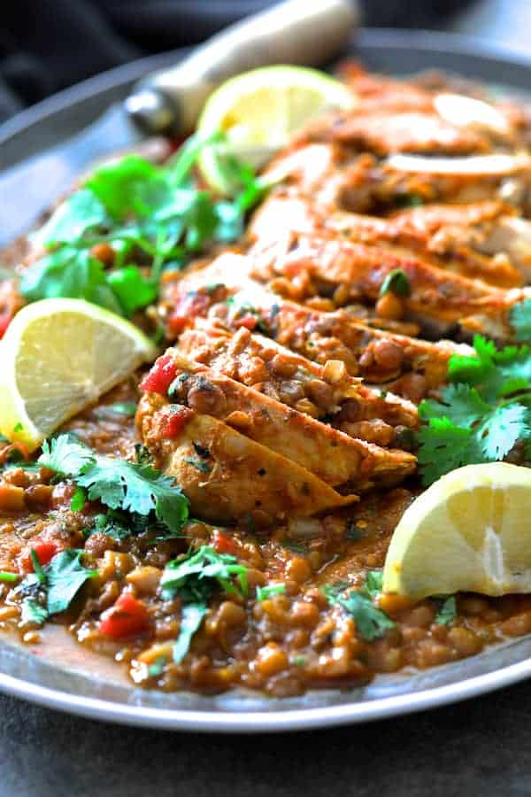 Slow Cooker Moroccan Turkey and Lentils - Close-up shot of finished dish on gray-rimmed platter garnished with cilantro and lemon wedges