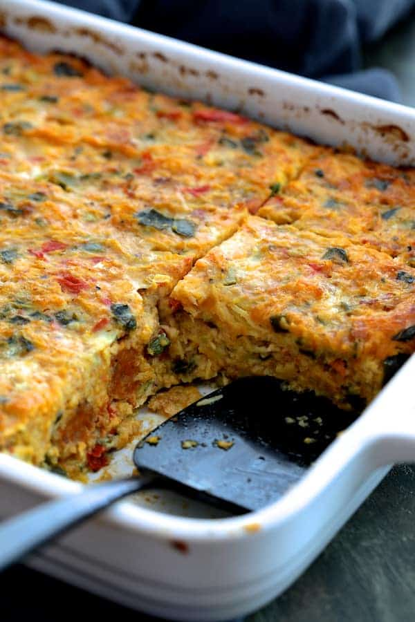 Spaghetti Squash Poblano and Chorizo Breakfast Casserole - Shot of casserole in white baking dish with pieces taken out with black server