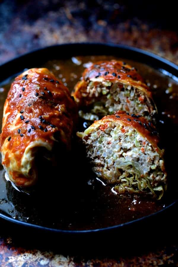Spicy Asian Pork Cabbage Rolls - Close-up of cooked cabbage rolls, sliced on black plate garnished with sesame seeds