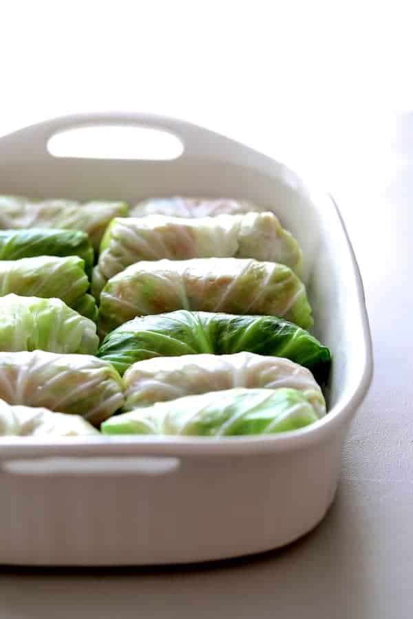 Spicy Asian Pork Cabbage Rolls - Uncooked cabbage rolls in white baking dish