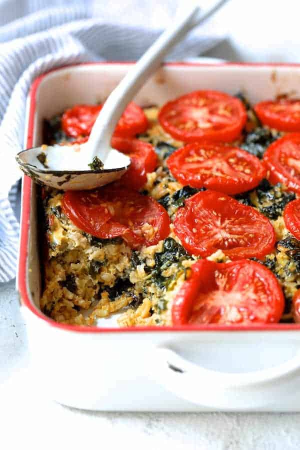 Brown Rice Cheddar Kale Casserole on white background with striped towel on wood trivet with white spoon with some served