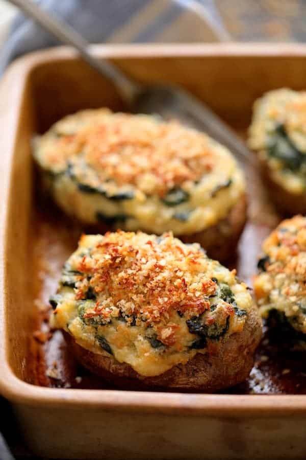 Spinach Parmesan Ranch Twice Baked Potatoes very close up in clay baking dish with serving fork and blue striped towel in the background