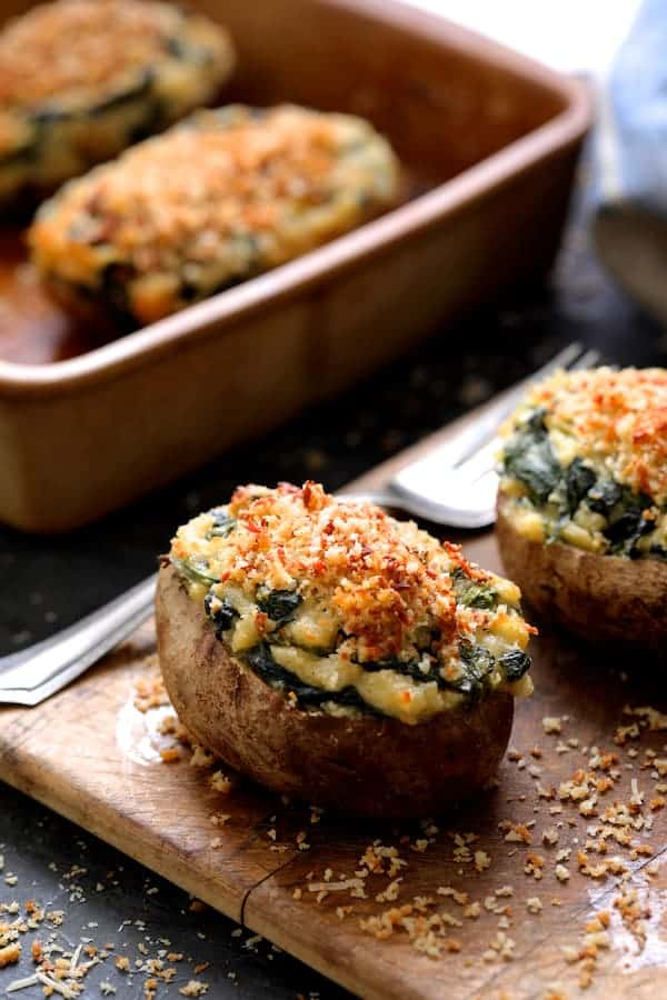 Spinach Parmesan Ranch Twice Baked Potatoes on small wooden cutting board with serving fork and clay baking dish in the background