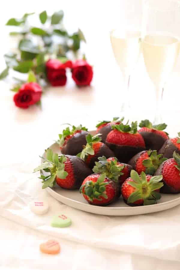 Steak au Poivre and Broiled Lobster Tail - Photo of three red roses, chocolate covered strawberries, champagne and conversation hearts on white linen background