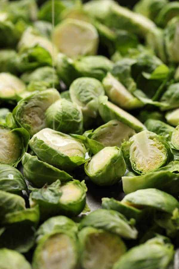 Sriracha Sweet Chili Roasted Brussels Sprouts - Halved raw Brussels sprouts on baking sheet being drizzled with oil