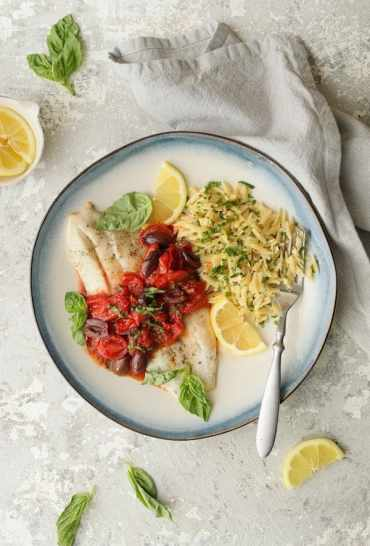 Baked Fish with Cherry Tomato Olive Sauce + Lemon Chive Asiago Orzo - Hero shot on light gray background with light gray napkin
