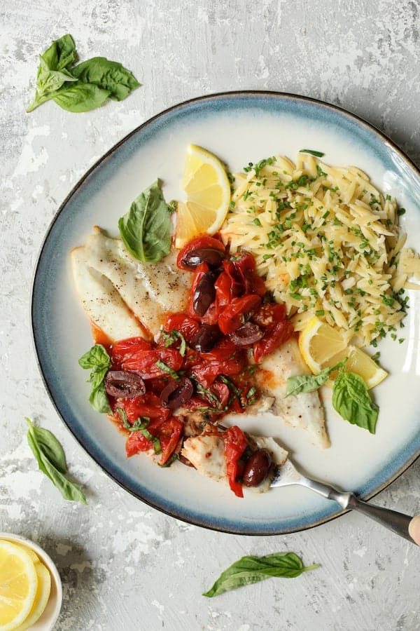 Baked Fish with Cherry Tomato Olive Sauce + Lemon Chive Asiago Orzo - Close-up shot on gray background with forkful of fish ready to eat