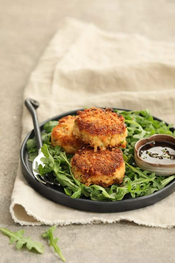 Tuna Kimchi Cakes with Soy Ginger Dipping Sauce - On plate over baby arugula