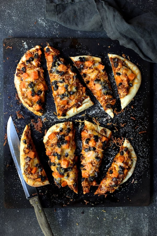 Chipotle Chicken Sweet Potato and Black Bean Flatbread Pizzas with Avocado Sour Cream - After baking sliced on wood cutting board