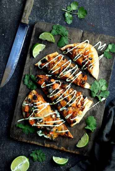 Chipotle Chicken Sweet Potato and Black Bean Flatbread Pizzas with Avocado Sour Cream - Hero shot on dark background, cut into wedges on dark wood cutting board garnished with lime wedges and chopped cilantro
