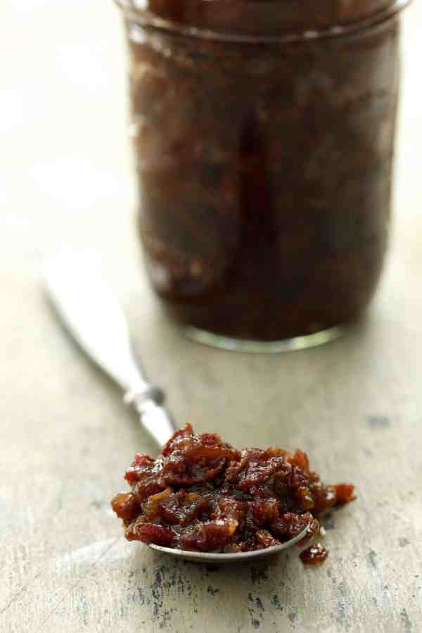 Grilled Burgers with Bacon Tomato Jam and Smoked Gouda - Close-up shot of bacon jam on spoon with glass jar of jam in the background