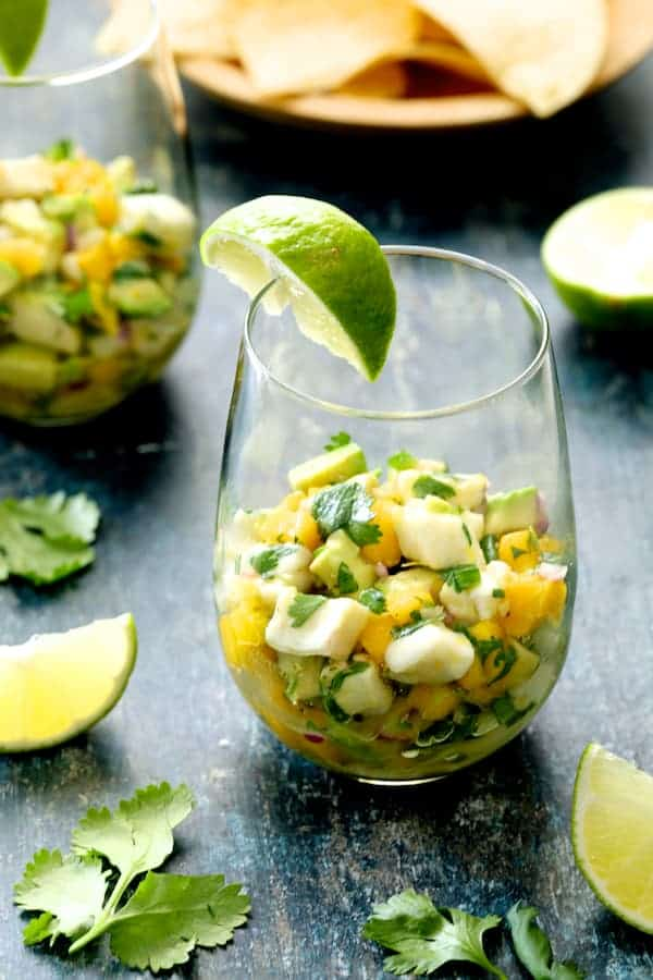 Halibut Ceviche with Mango and Avocado in glass garnished with lime wedge