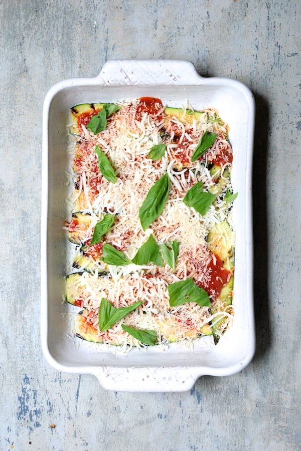 Italian Summer Vegetable Casserole - First layer in white baking dish of zucchini, some marinara and fresh basil