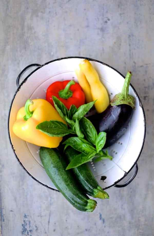 Italian Summer Vegetable Casserole - Overhead shot of bell peppers, zucchini, yellow squash, eggplant and fresh basil in white colander