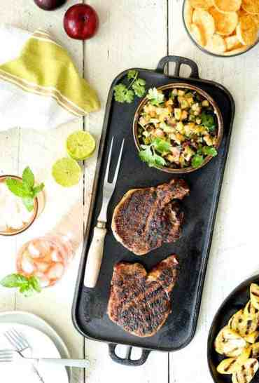 Southwestern Spice Grilled Pork Chops with Plum Jalapeño Salsa - Overhead hero shot of pork chops with salsa, chips and tea on white wooden background