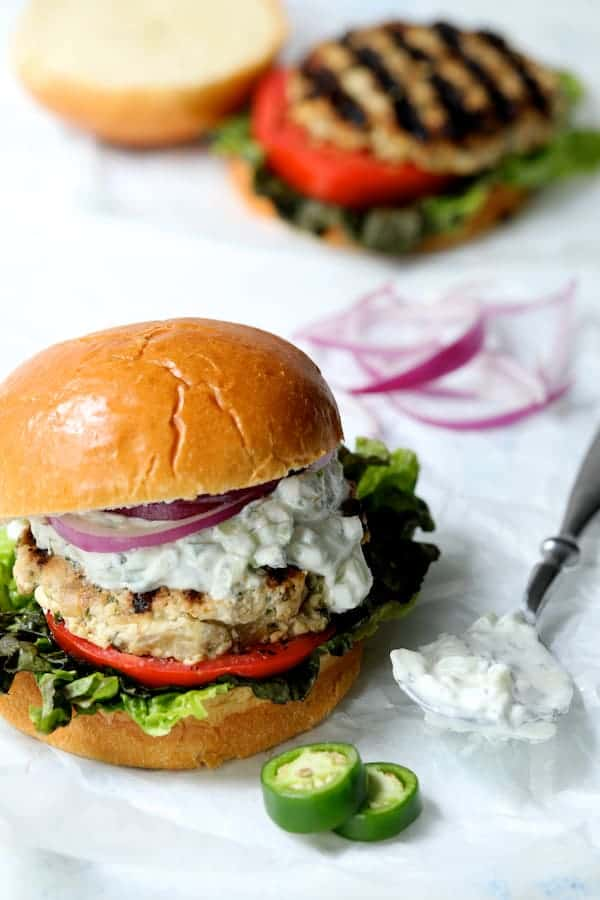 Chicken Zucchini Feta Burgers with Jalapeño Tzatziki - Shot of burger with tzatziki on spoon next to burger with jalapeno and onions nearby