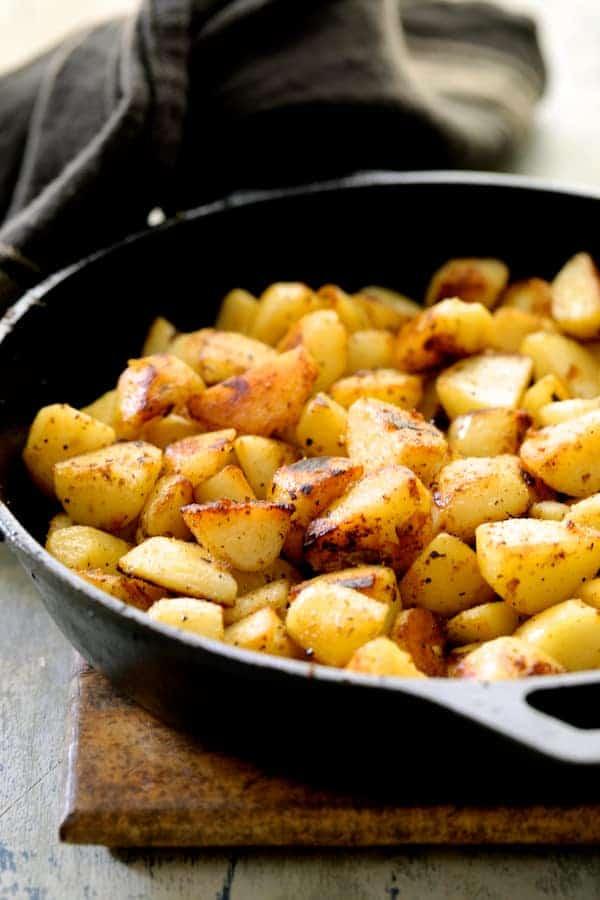 Patatas Bravas Chilenos - Browned potatoes in cast iron skillet