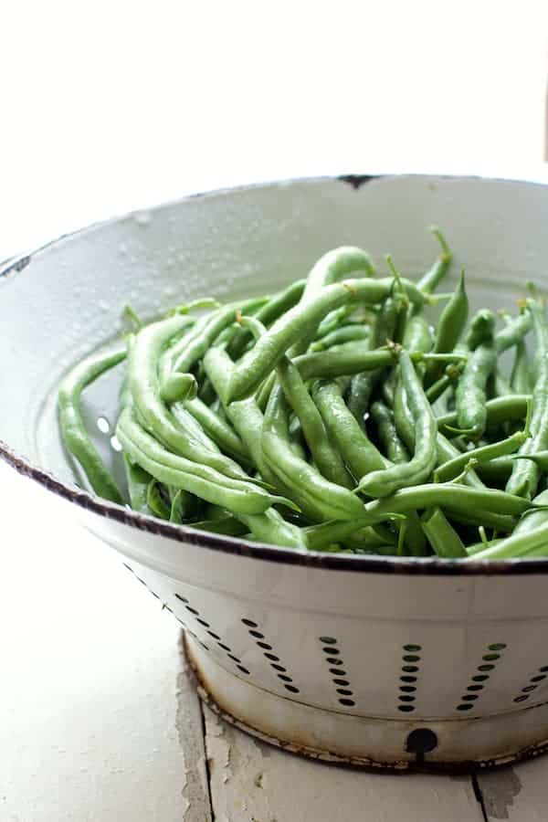 Skillet Charred Green Beans with Goat Cheese Chipotle Butter - Raw green beans in white colander
