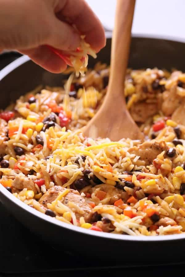 Southwestern Chicken Orzo and Black Bean Skillet - Cheese being added to finished dish
