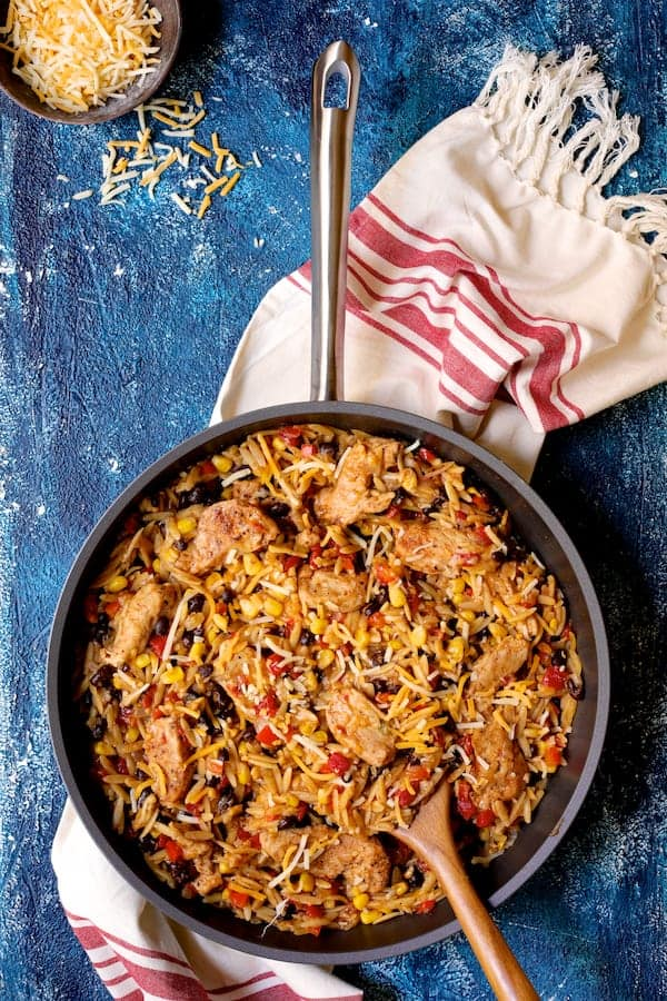 Southwestern Chicken Orzo and Black Bean Skillet - Overhead shot of finished dish on blue background with red and white striped towel
