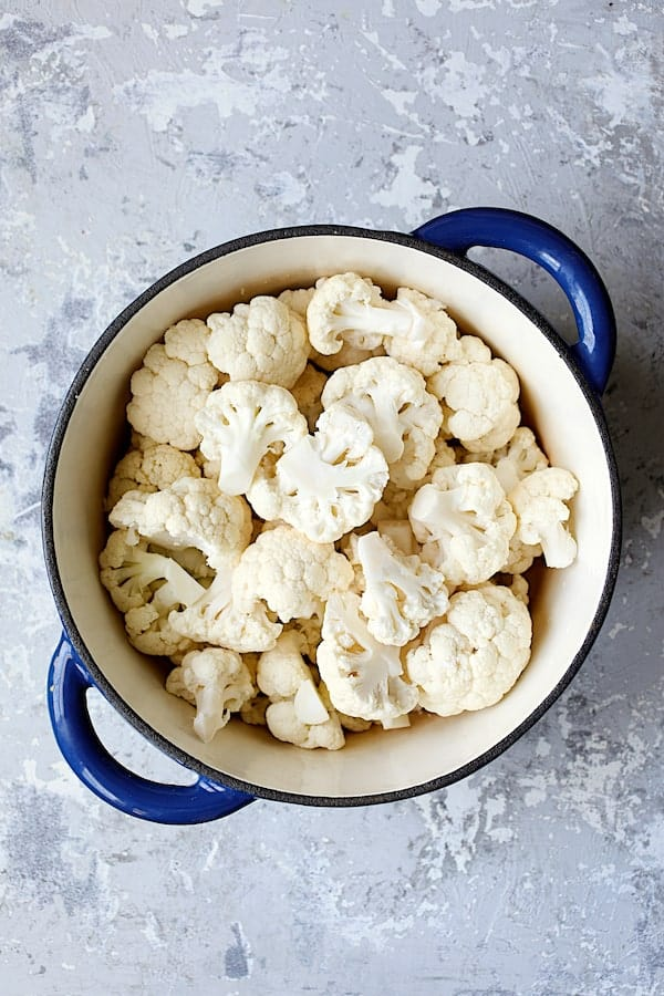 Cauliflower White Bean Puree - Overhead shot of cauliflower florets in blue Dutch oven ready to be cooked