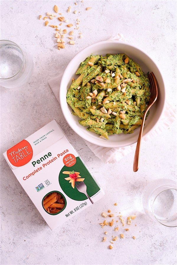 Modern Table Pasta with Creamy Cashew and Spinach Pesto Sauce - Overhead shot of a bowl of the finished pasta dish with box of Modern Table pasta
