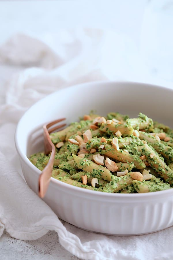 Modern Table Pasta with Creamy Cashew and Spinach Pesto Sauce - Front view of finished pasta dish in white bowl