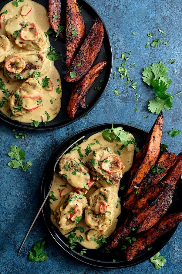 Spicy Tahini Pork Medallions with Harissa Roasted Sweet Potato Wedges - Hero overhead shot of dish on blue background