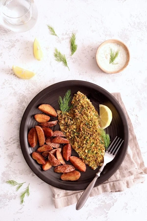 Pistachio-Crusted Fish with Lemon-Dill Aioli - Overhead shot of dish served with roasted potatoes garnished with lemon slices and dill sprigs on black plate
