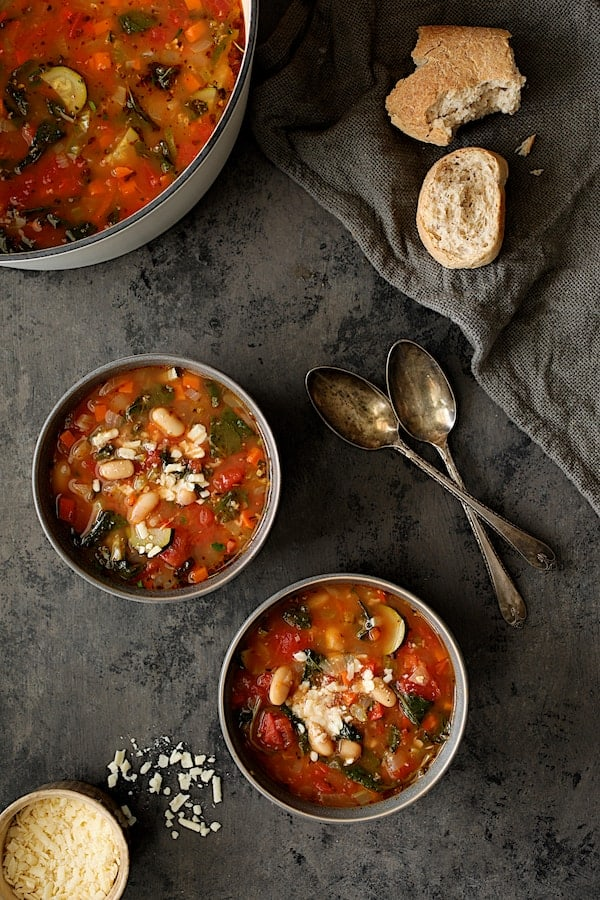 Smoky Spanish Vegetable and White Bean Soup with Kale - Overhead shot of soup in two bowls with cheese and with two spoons and broken bread on gray napkin