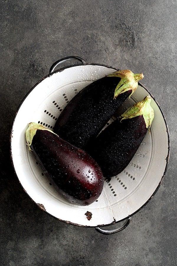 Turkish Eggplant Casserole - Imam Bayildi - Overhead shot of three eggplant in antique white colander